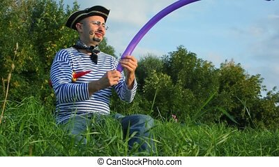man in pirate costume in park makes sword out of air balloon