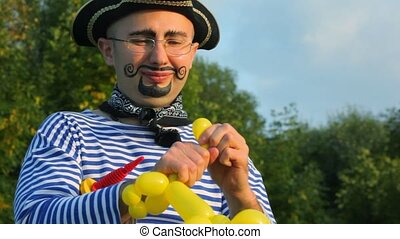man in pirate costume makes poodle out of air balloon in...