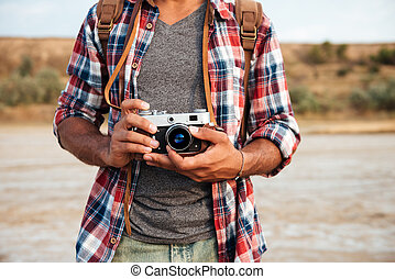Man in plaid shirt holding old vintage photo camera