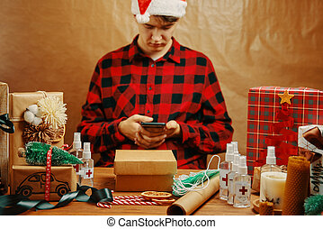 Man in plaid shirt with mobile phone in holiday decorations.