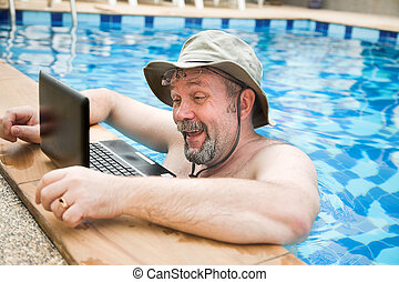 man in pool with laptop