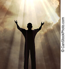 man in praise - Man holding arms up in praise against a...