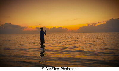 Man in prayer opens his hands to the sunrise sun and sky