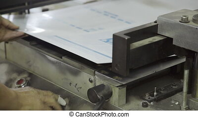 man in printing bends corners on sheet of paper on machine....