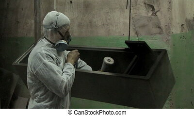Man in protect suit painting with powder