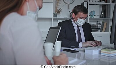 Man in protective medical mask helping his colleague to prepare document on your computer