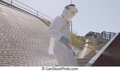 Man in protective suit disinfects street with an antiseptic ...