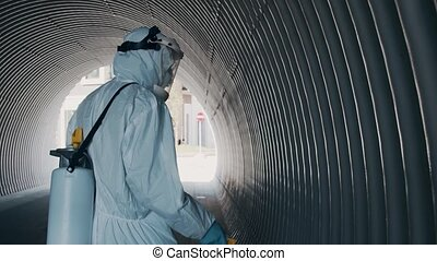 Man in protective suit disinfects subway tunnel with an ...