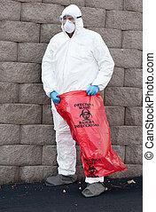 hazardous waste - man in protective suit holding a hazardous...
