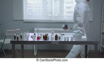 Man in protective workwear and mask work in the laboratory...