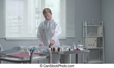 Man in protective workwear check chemical test tube in the laboratory
