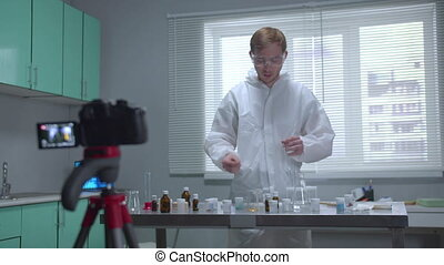 Man in protective workwear pour liquid into tube on camera ...
