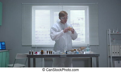 Man in protective workwear smell things in the laboratory - ...