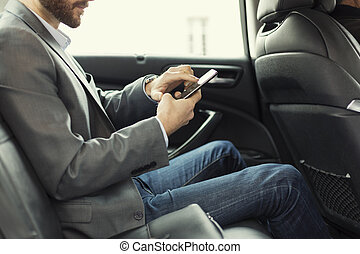 Man in rear of the car. Typing text message on mobile phone