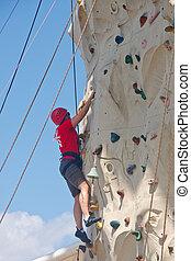 Man in Red Shirt Climbing Rock Wall