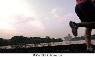 Man in red tshirt running against evening sky. Super slow motion steadicam shot