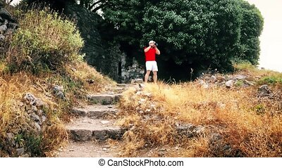 Man in red tshirt takes landscape photos with his camera on...