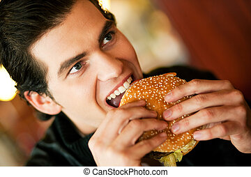 Man in restaurant eating hamburger