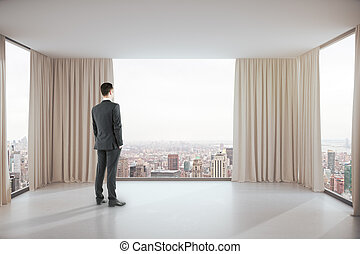 Man in room with city view