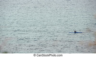 Man in row boat at open sea, off-season time