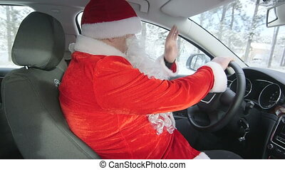 Man in Santa Claus costume driving car in snow through winter forest