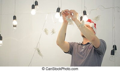 Man in Santa Claus hat decorates room for new year inside