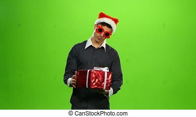Man in Santa Claus hat holding presents. Christmas. green screen