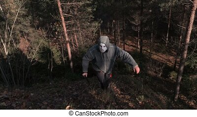 Man in scary Halloween mask and machete step up on the hill