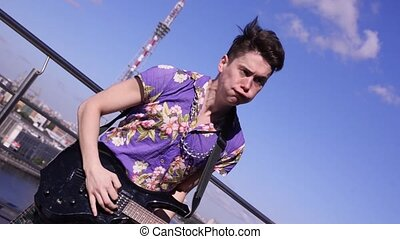 Man in scotland skirt, shirt play electric guitar on seafront in sunny day. Dance. Rock and roll