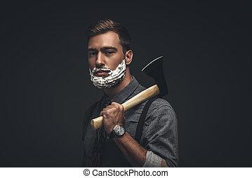 Man in shaving cream holding axe