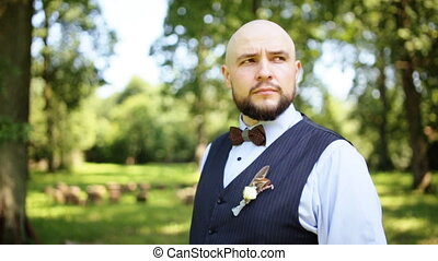 Man in shirt and vest with bow tie and walking in park and looking away