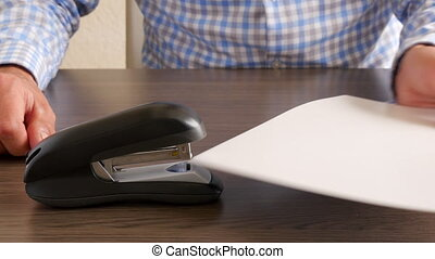 Caucasian male in blue grey casual business shirt using stapler on paperwork with hand