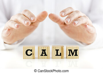 Man in shirtsleeves holding his hands protectively above wooden cubes with the word Calm.