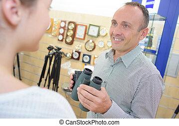 Man in shop holding binoculars