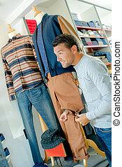 Man in shop holding trouser leg on mannequin