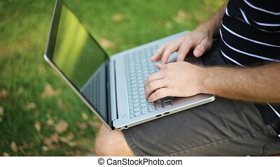 man in shorts sitting on a bench in the park with a laptop