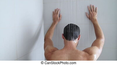 Man in shower showering in bathroom at home. Unrecognizable person from behind warm bath in modern bathroom. hands against wall maybe tired and depressed or maybe relaxing serene.