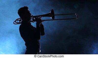 Man in silhouette playing on trombone. Smoky studio, slow motion