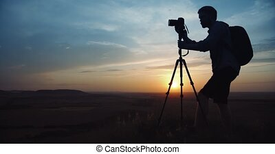 Man in silhouette using tripod for taking pictures of sunset...