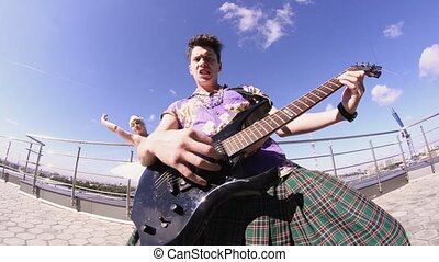 Man in skirt play electric guitar on seafront in sunny day. Girl dance in ballerina suit. Rock