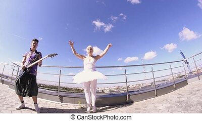 Man in skirt play electric guitar on seafront, sing in camera. Girl dance in ballerina suit. Crazy