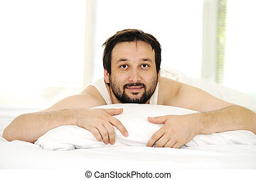 Man in sleeping bed, morning time