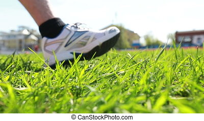 man in sneakers on green grass