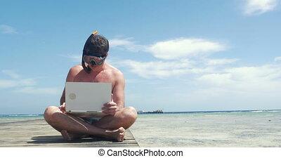 Man in snorkel using pad on pier - Young man in snorkel...
