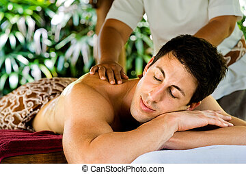 Man In Spa - An attractive young man enjoying a back massage...