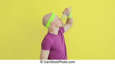 Man in sportswear is drinking water from bottle on yellow background, side view.