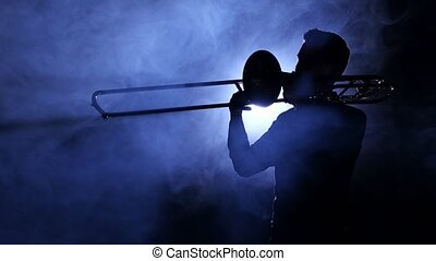 Man in spotlight in smoky studio plays on trombone, dark silhouette of man in smoke is visible to waist and sideways to viewer, playing slow melody, professional musician, rear searchlight