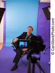 man in studio - businessman being videotapped in studio over...