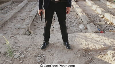 man in suit aiming a gun at the camera and shoot