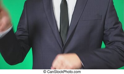 man in suit and tie holding a coin bitcoin in his hand. He throws it. green background, 4k, slow motion
